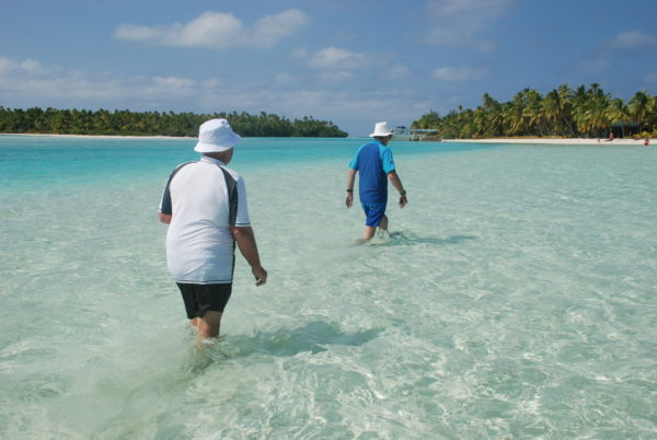 Two people wading through Aitutaki Lagoon