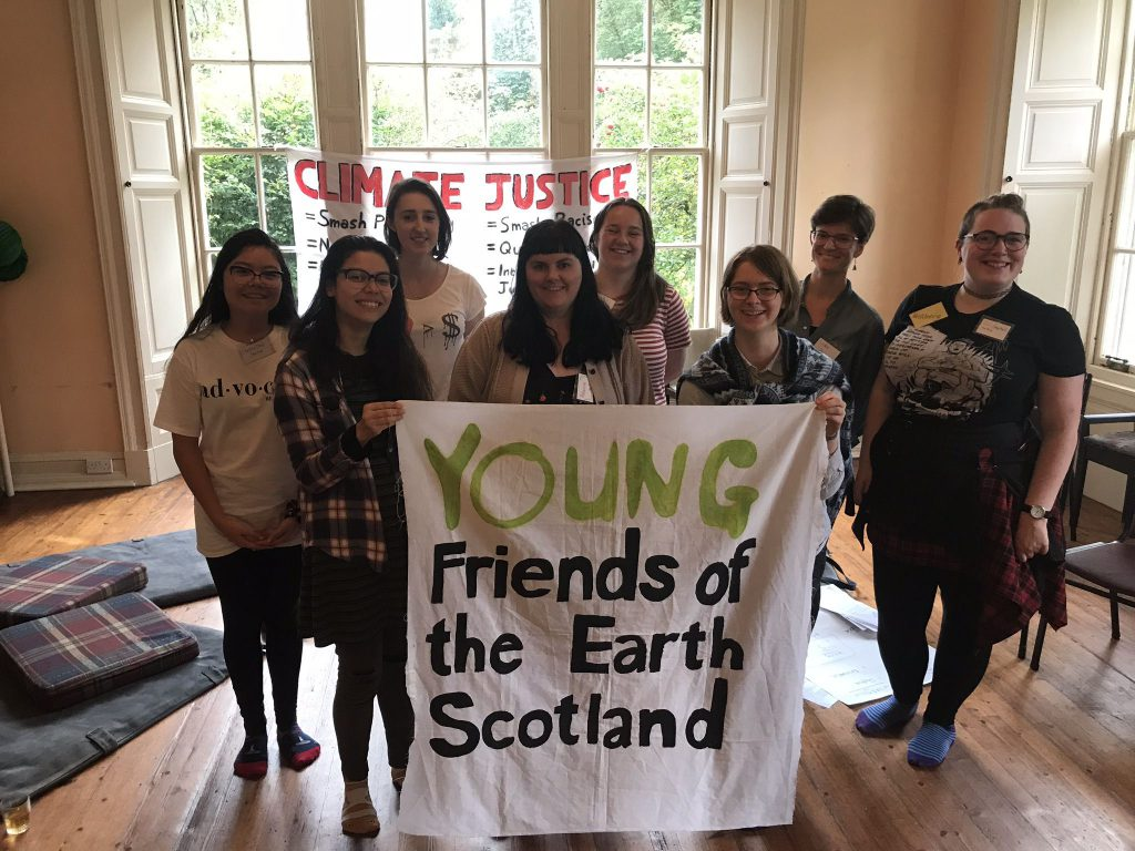 A group of eight people hold a banner reading Young Friends of the Earth Scotland