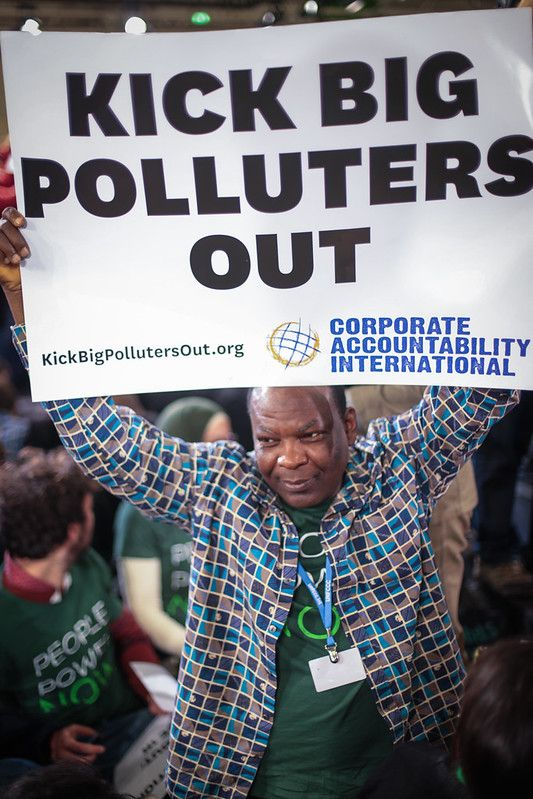 Man holding 'Kick Big Polluters Out' sign