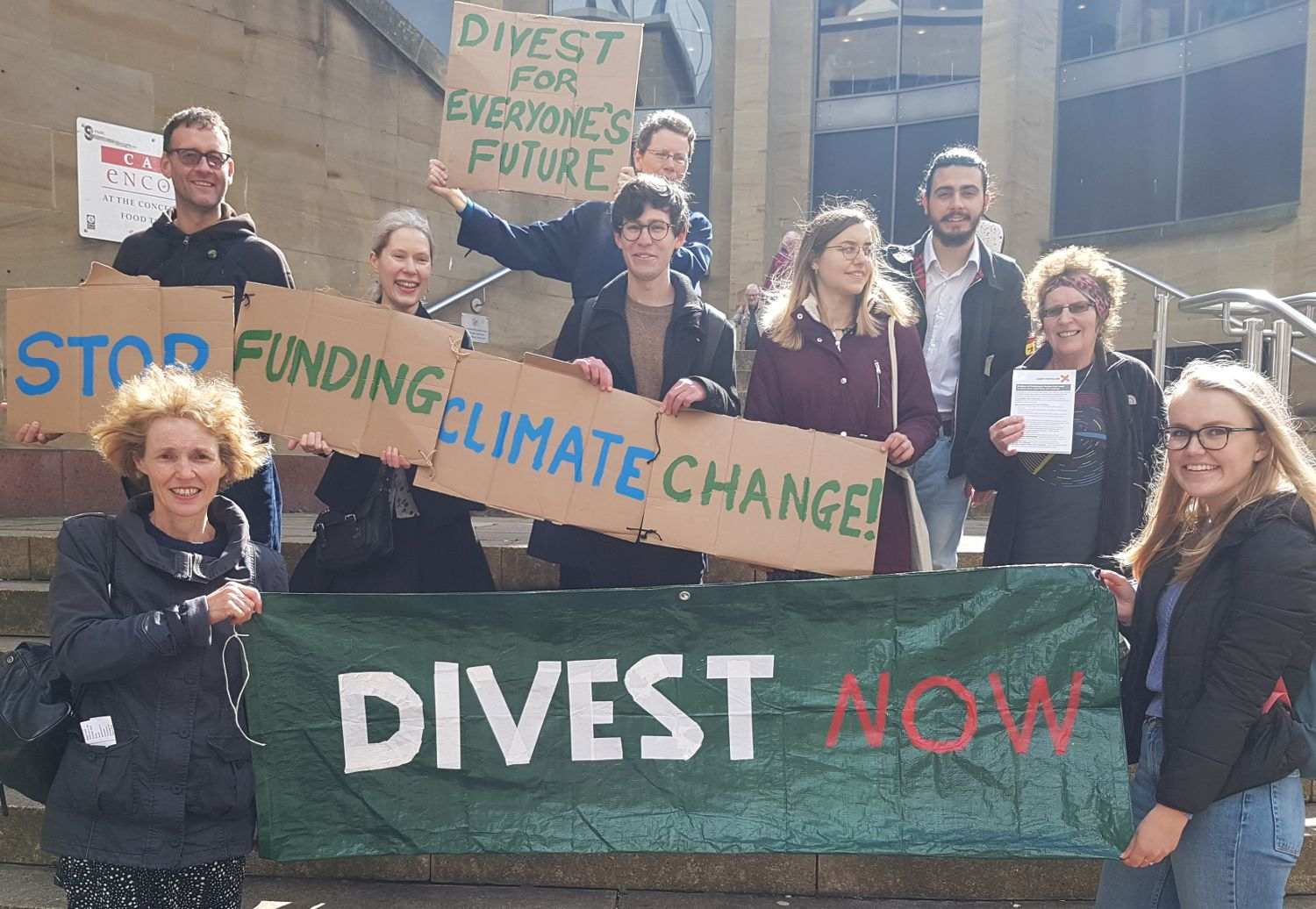 Activists hold a banner saying 'Divest Now'.