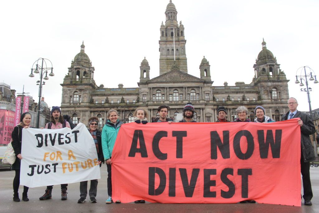 Protestors hold a banner saying 'Act Now Divest' in George Square, Glasgow