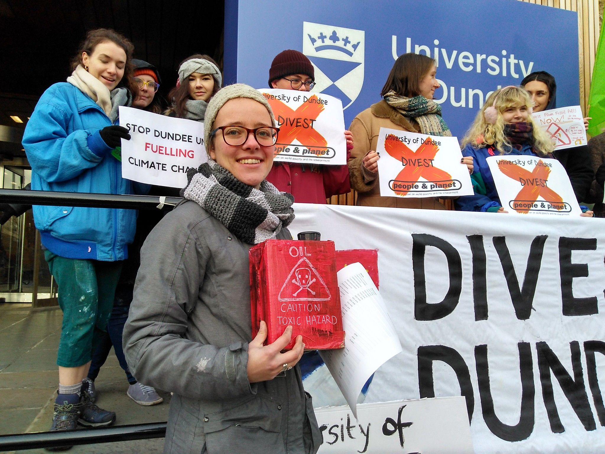 Students hold placards reading 'University of Dundee Divest - People & Planet' and Stop Fundee Uni Fuelling Climate Change'.