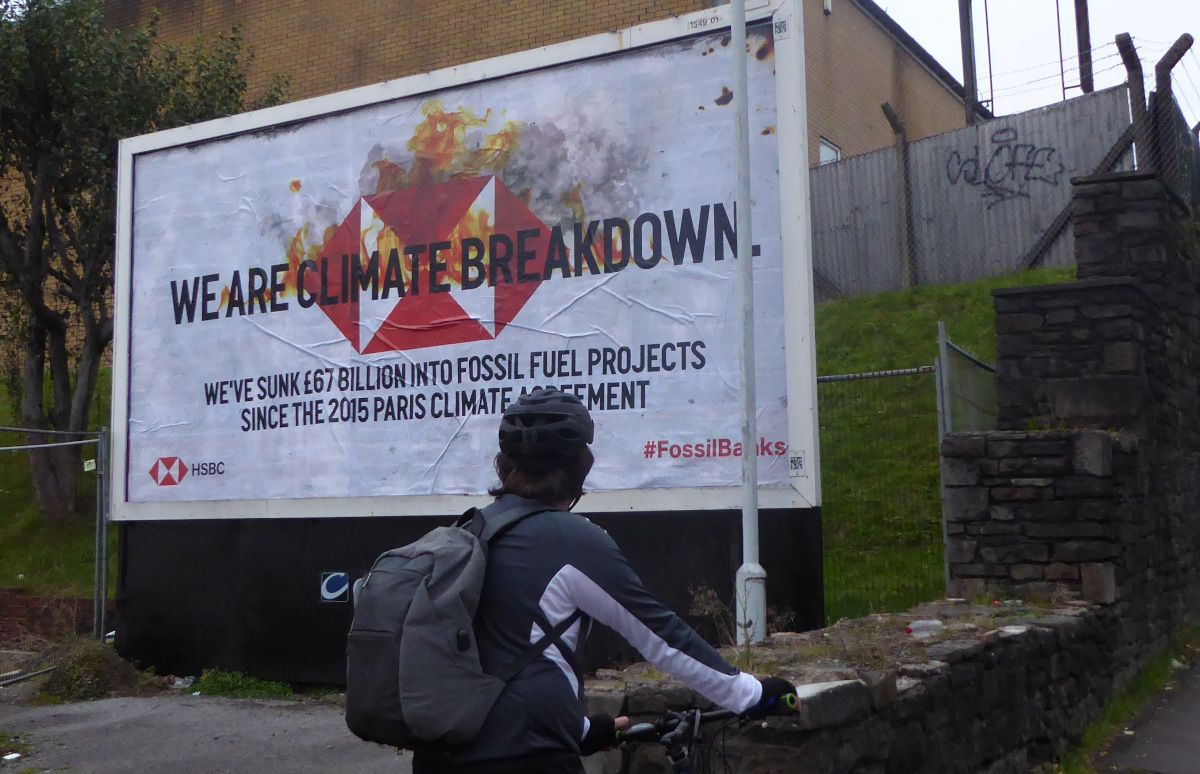Billboard reads 'We are climate breakdown. We've sunk 67 billion into fossil fuel projects since the 2015 Paris climate agreement.'