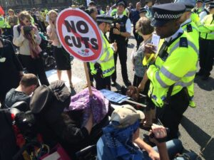 wheelchair users holding placards reading no cuts face up to police officers on Westminster bridge